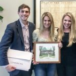 Image of couple holding a framed watercolor painting of their new home. They are standing next to realtor Laura Bonck.