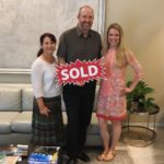 "Image of couple holding a red sign that says ""Sold"", standing next to realtor Laura Bonck."