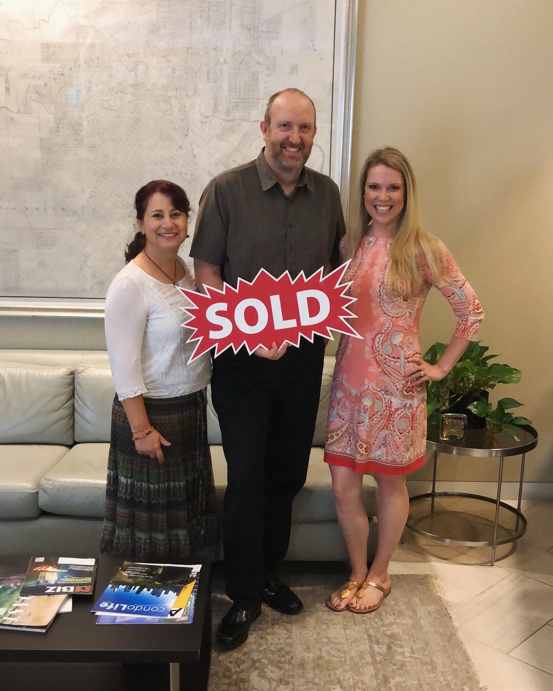 """Image of couple holding a red sign that says """"Sold"""", standing next to realtor Laura Bonck."""